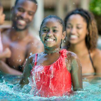 Happy family having fun in swimming pool